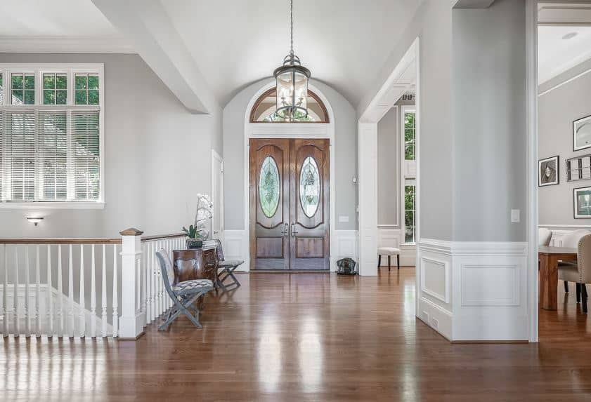 The light gray cove ceiling of this foyer is adorned with a lantern-like pendant light hanging over the hardwood flooring that blends with the wooden main doors that has an elegant arched transom window.