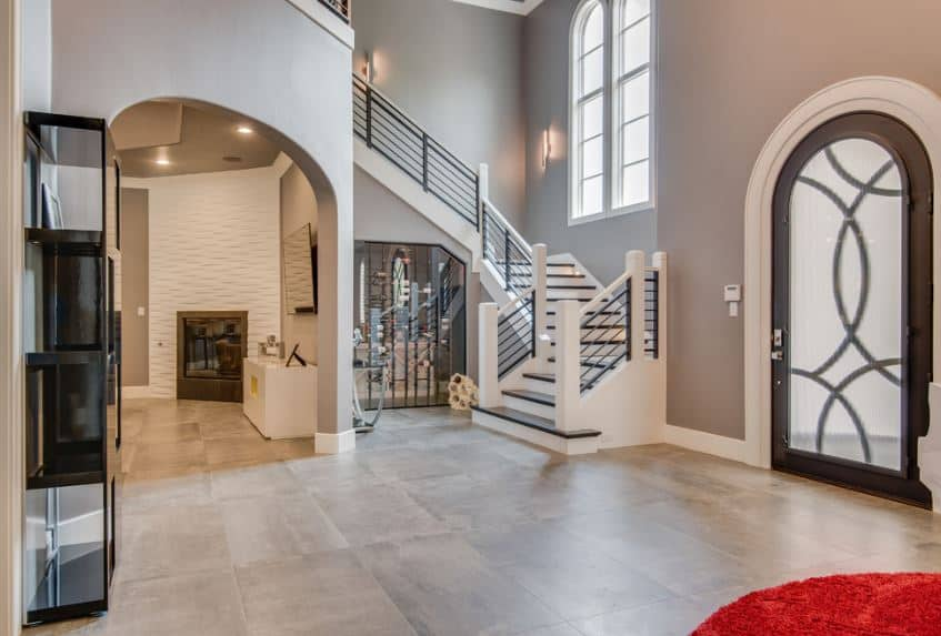 The arched main door is dominated by a frosted glass panel that brings in natural light to the marble flooring that complements the white molding of the gray walls adorned with a modern shelving across from the door.
