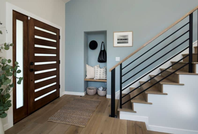 The charming wooden main door has horizontal stripes of frosted glass that matches with the single side light. This matches well with the white molding of the blue wall and hardwood flooring that has a brown woven area rug.