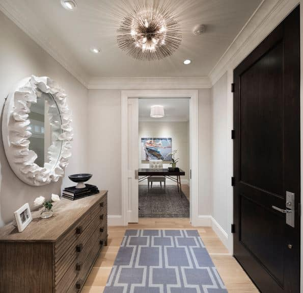 This small foyer is dominated by the peculiar eccentric elements of the wall-mounted circular mirror with frills on the frame as well as the brilliant sun-like pendant light hanging from the white ceiling over the gray patterned area rug.