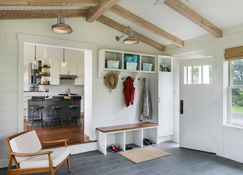 This cozy and homey foyer has a mudroom with a wooden bench that has partitions beneath it for a shoe rack and hooks mounted on the white wall above it for the coats and hats. This is contrasted by the gray flooring and exposed wooden beams of the cathedral ceiling.
