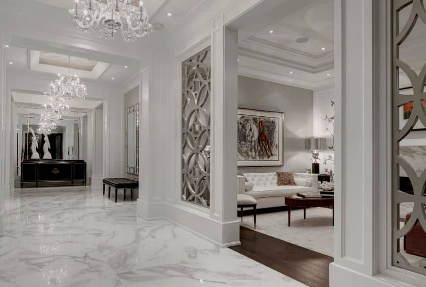This wide and bright foyer has white marble flooring that is complemented by the white tray ceiling and walls adorned with a wall-mounted silver mirror above a dark cushioned bench. These are all illuminated by the brilliant white chandelier.