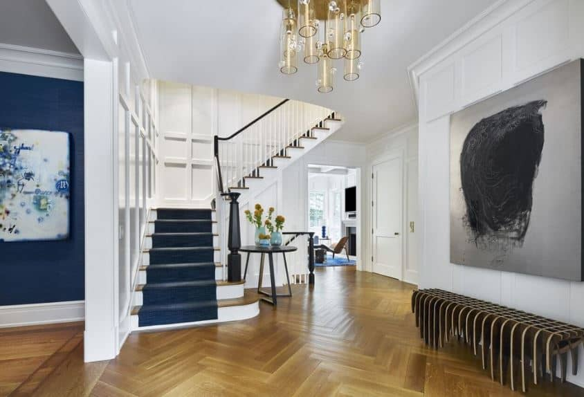 The herring bone pattern of the hardwood flooring is a nice complement to the white walls that have elegant finishing accented with a gray painting above a modern bench that has a peculiar design.