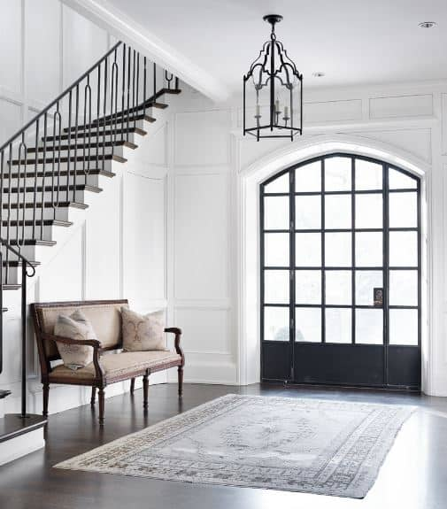 The main door and its side lights are dominated by the square panels of frosted glass that brighten up the white walls and its elegant finish that matches with the cushioned bench and the dark hardwood flooring covered with a patterned area rug.