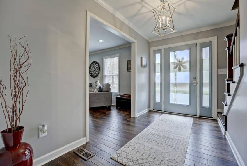 This foyer has a lantern-like pendant light that cast warm yellow light against the gray walls that have white molding that is reflected by the main door and its side lighting contrasting the dark wooden flooring.