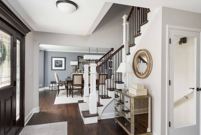 Upon entry of this foyer, you will be welcomed by a mirrored drawer that is topped with a wall-mounted circular mirror that stands out against the white walls contrasted by the dark main door and dark hardwood flooring.