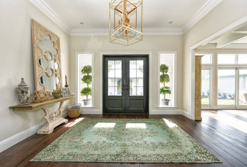 The highlight if this foyer is the brilliant and cheerful light green patterned area rug covering the hardwood flooring. This is paired with a curved beige console table topped with various decors and a large mirror matching with the lantern pendant light.