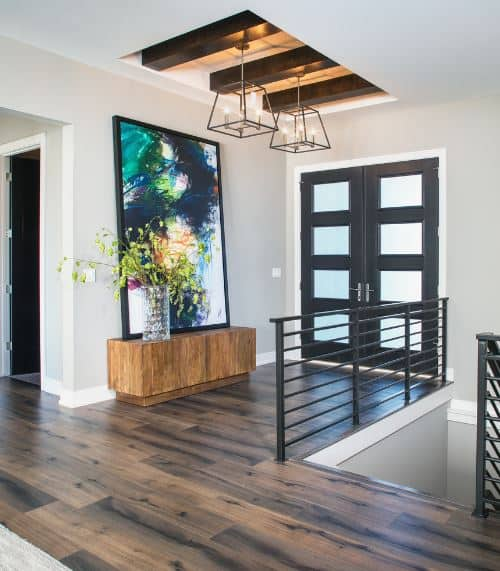 The dark frames of the main doors that have frosted glass panels pairs well with the wooden exposed beams on the middle tray of the white ceiling supporting a pair of lantern pendant lights with a background of a colorful painting.