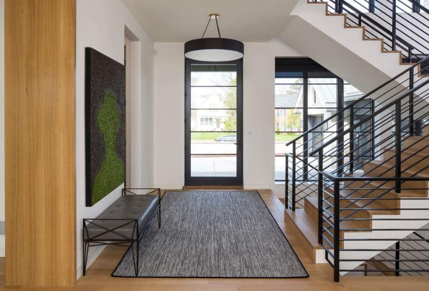 The brilliant green and black silhouette painting above the cushioned gray bench matches with the gray are rug over the hardwood flooring that is illuminated by the glass panels of the main door with black frames matching the railings.