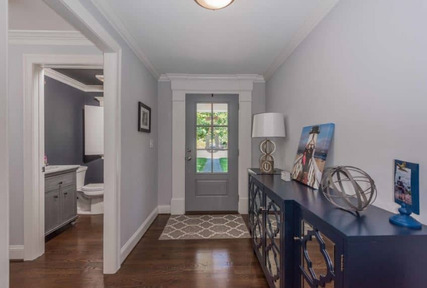 The gray main door is perfectly paired with the light gray walls that are contrasted by the navy blue mirrored cabinetry on the side that bears decors on its top as well as a painting that bring a dash of color to the hardwood flooring and light gray ceiling.