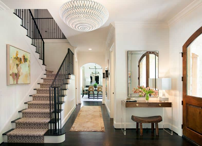 This small foyer has a dome semi-flush light mounted on the white ceiling that blends with the white walls and contrasts the dark hardwood flooring that is complemented by the console table that has see-through plastic legs.