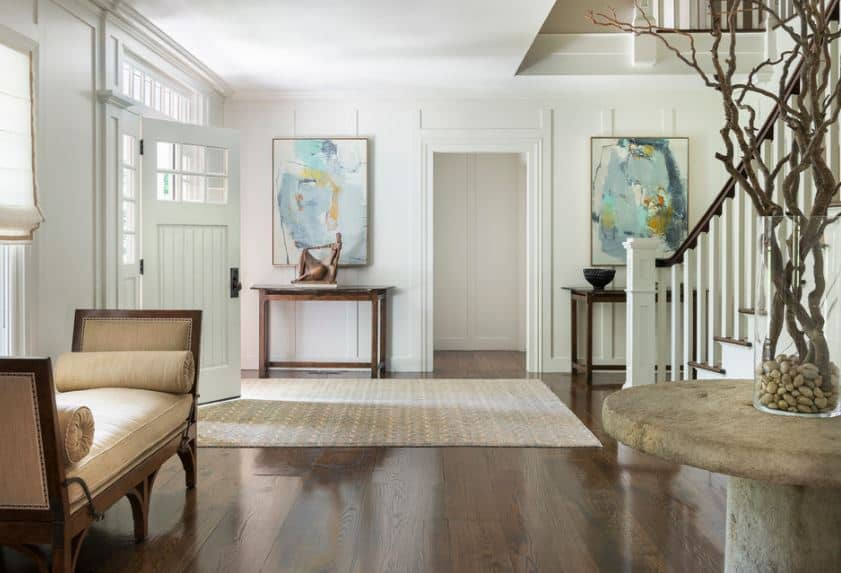 This a cozy foyer with a gray patterned area rug over the dark hardwood flooring that is contrasted by the white walls and ceiling. The main door is flanked by a console table on the side topped with a painting and a cushioned bench.