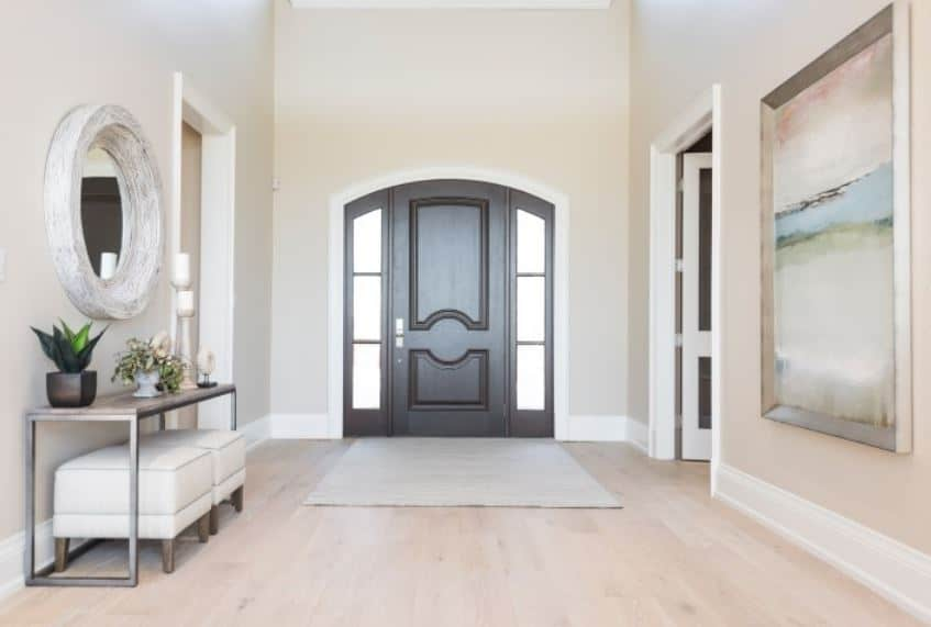 The light hardwood flooring that is topped with a light gray area rug matches well with the beige walls that is trimmed with white molding that contrasts the dark arched main door surrounded by glass side lighting and transom window.
