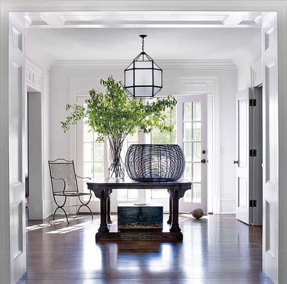 This bright and welcoming Transitional-Style foyer has a dark hardwood flooring with a dark wooden table in the middle bearing plants in a glass vase as well as a spherical basket that stands out against the white walls with an elegant finish.