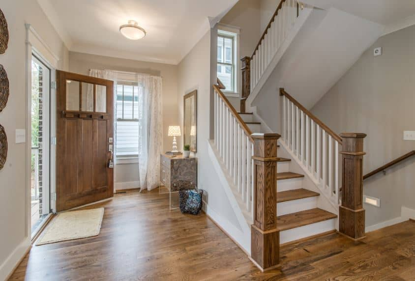 This is a foyer beside the white staircase that has wooden steps blending in with the hardwood flooring and the wooden main door that opens to the light gray walls and white ceiling with a small semi-flush lighting.