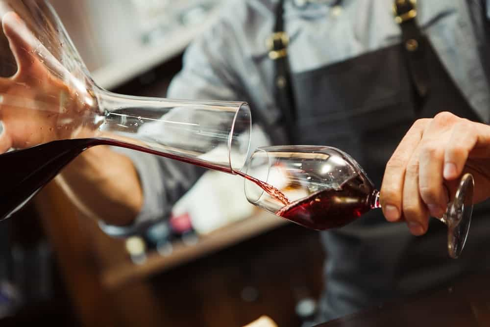 Pouring red wine from a decanter to a wine glass.