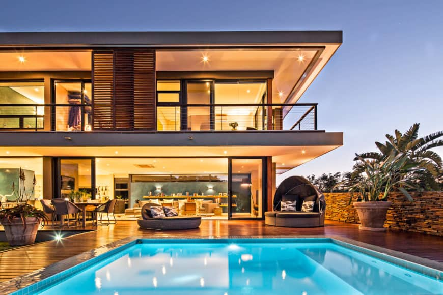 A contemporary house featuring a deck with multiple relaxing lounges and a swimming pool.