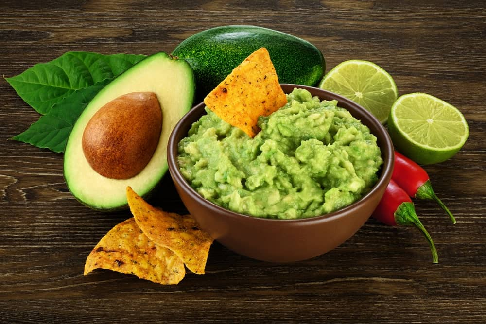 A bowl of avocado mash with a tortilla sticking on top surrounded by a whole avocado, a cut avocado, cut limes, chilis, and nacho tortillas.