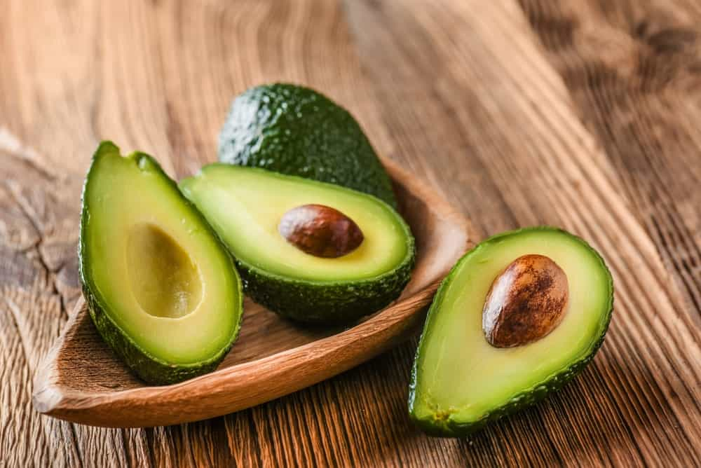 Whole and cut avocados on wooden bowl.