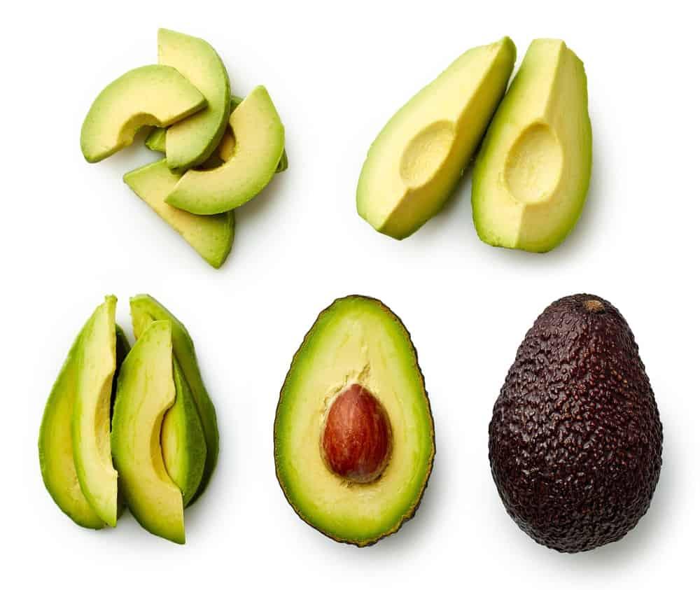 Cut slices of avocado and a ripe uncut avocado.