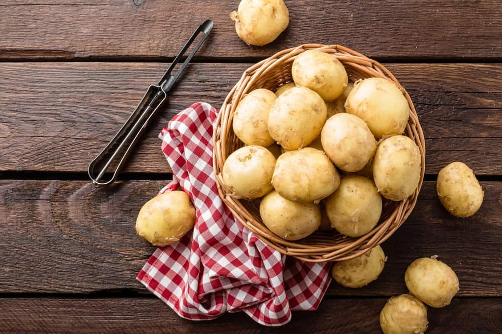 A bowl of potatoes on a wooden desk with a tong and tablecloth.
