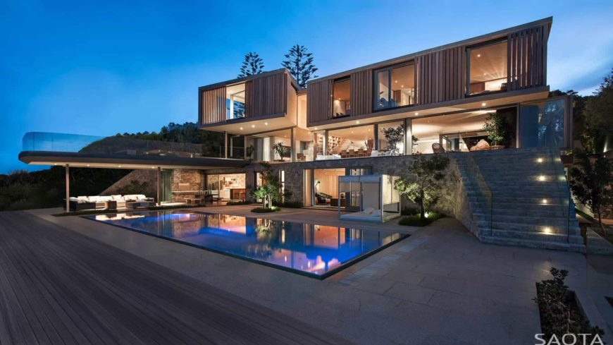 A large contemporary house featuring a wide outdoor area with a swimming pool and an outdoor living.