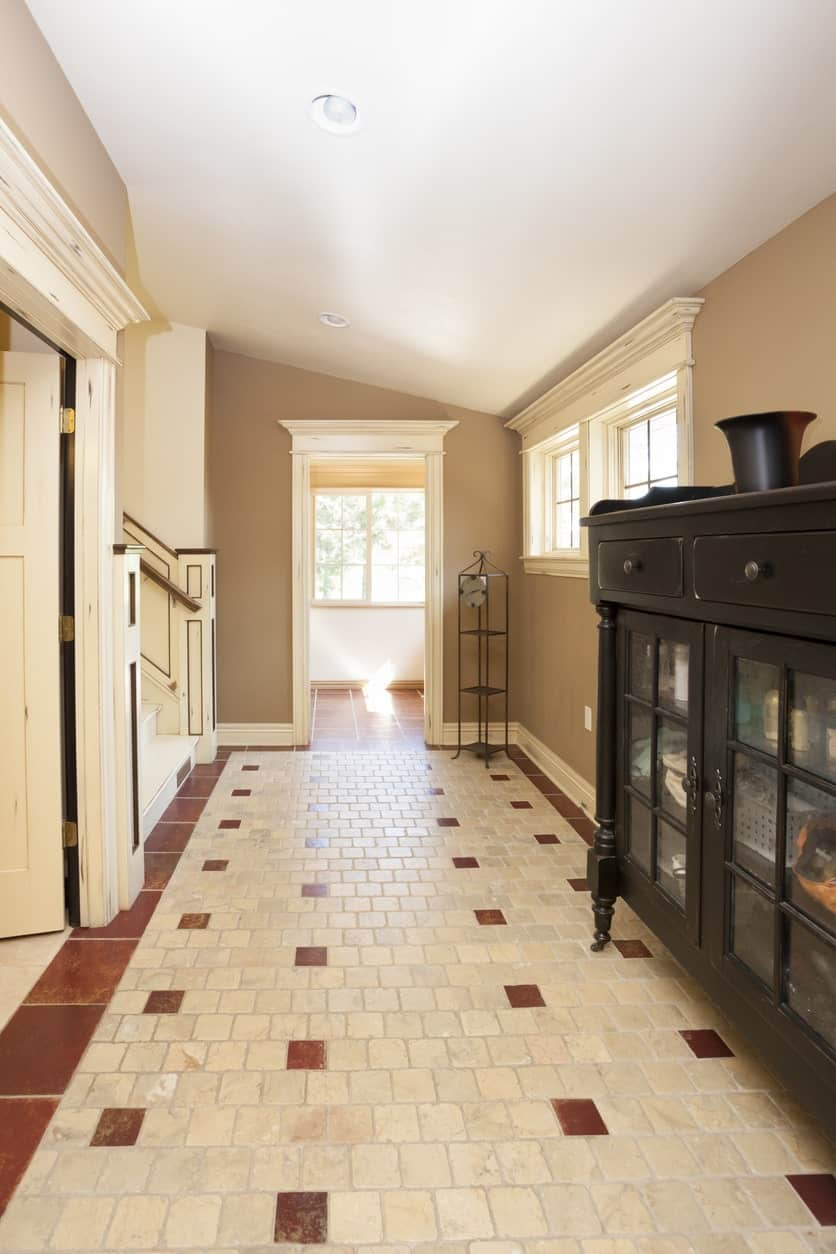 This foyer boasts a black wooden storage cabinet and metal shelving over brick flooring that's bordered with red tiles.