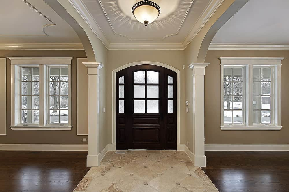 Sophisticated foyer with a dark wood arched front door fitted with glass panels and lined with white columns that are attached to the beige walls.