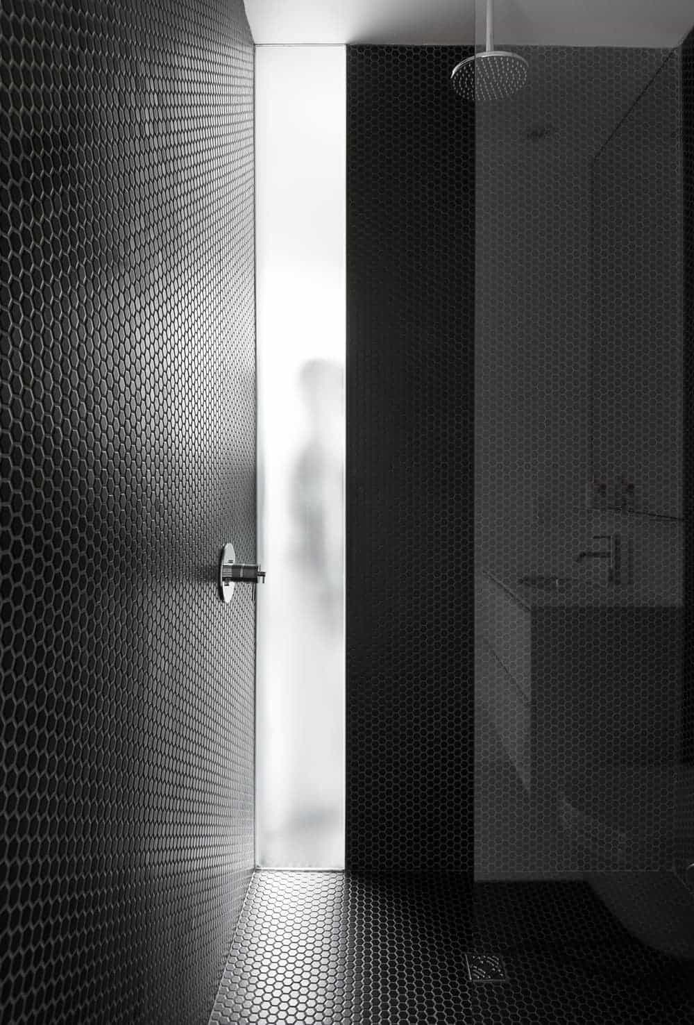 This shower area boasts small black hexagonal tiles that dominate the walls and flooring. The shower area is separated from the rest of the bathroom by a half glass wall.