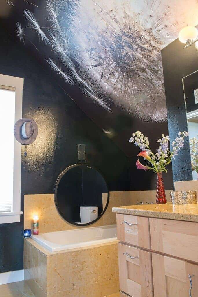 The black shed ceiling over the bathtub has a dandelion mural that brightens up the black walls. The bathtub is inlaid with beige marble tiles that extend to the flooring.