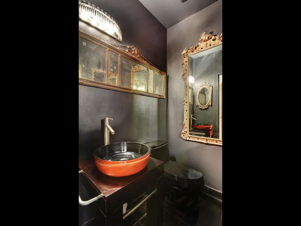 This dark-gray walled bathroom features the sleek black toilet that pairs well with the black vanity topped with an orange sink.