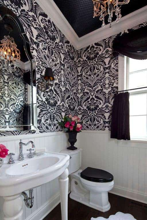 The classy black and white wallpaper has floral designs that add complexity to the simple white wooden finish and porcelain black and white toilet.