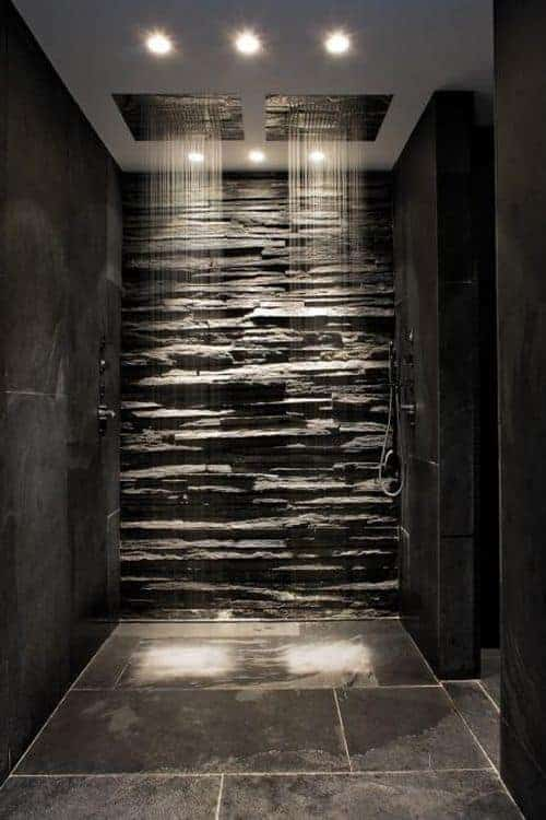 This lovely walk-in shower area has a textured stone wall that contrasts the black-tiled walls and setting a nice background for the overhead showers.
