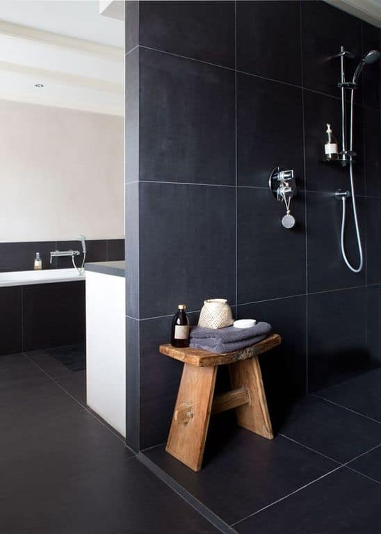 The black tiles of the walls and floor are paired with silvery metal shower fixtures and a lovely wooden stool.