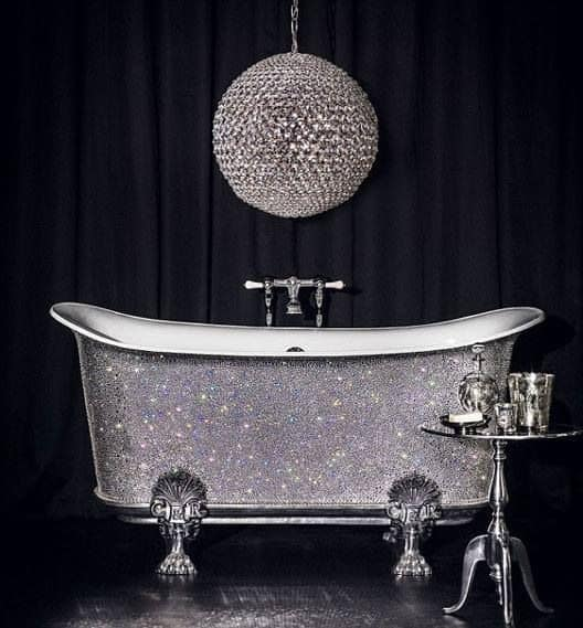 There is a peculiar disco ball-like pendant light hanging over the matching silvery freestanding bathtub that sparkles against the black curtain background.
