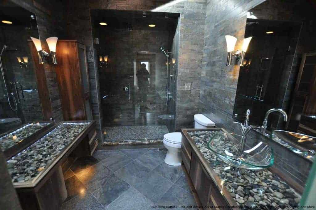 The brilliant glass sink is paired with a glass countertop over decorative stones that matches the walls and flooring.