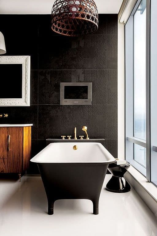 The white flooring makes the black freestanding bathtub stand out along with the rustic basket over the pendant light.