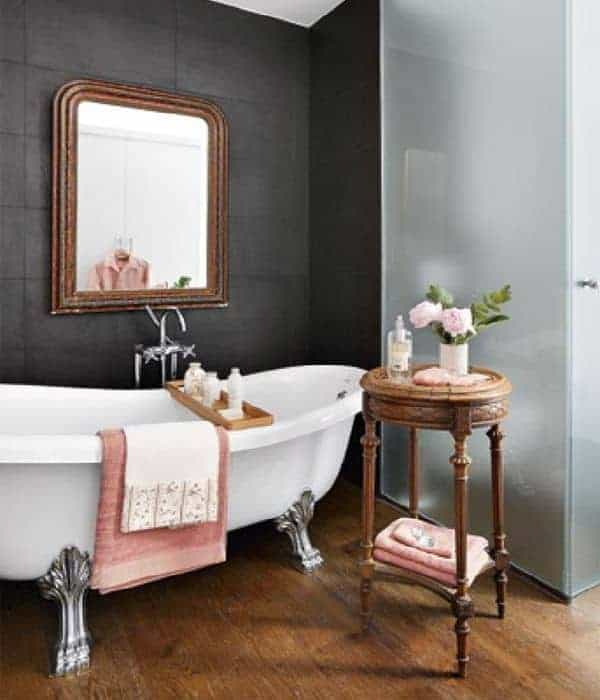 An elegant freestanding bathtub with intricate silver legs contradicts the black wall beside it that has a wall-mounted mirror.