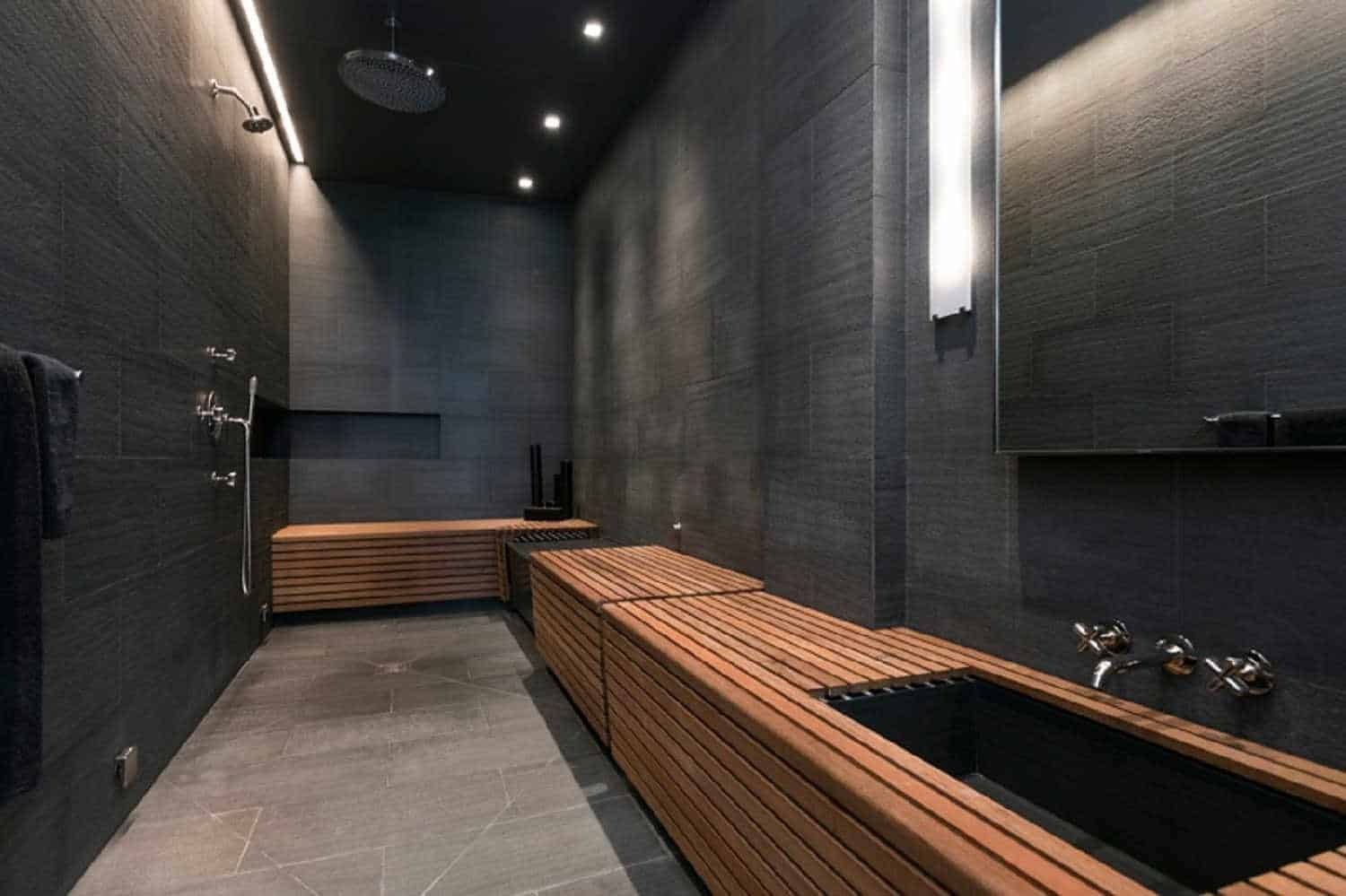 This elongated and black-tiled bathroom is dominated by a wooden L-shaped structure that serves as vanity and bench in a sauna-style design.