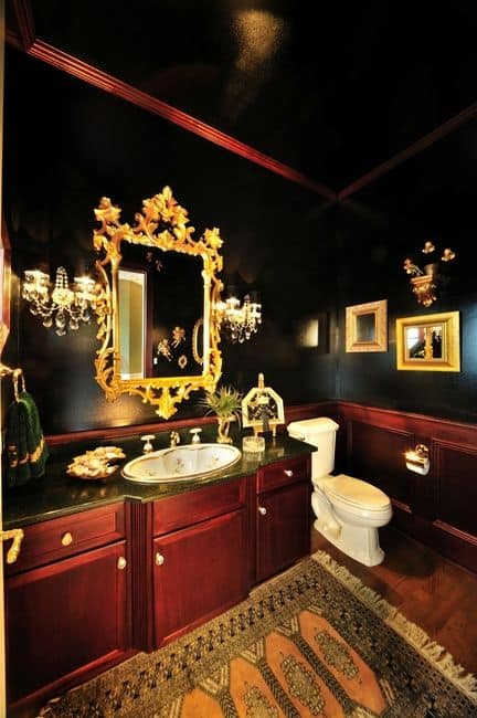 The black walls of this bathroom are brightened by the golden hues of the intricate vanity mirror and the wall-mounted lamps flanking it.