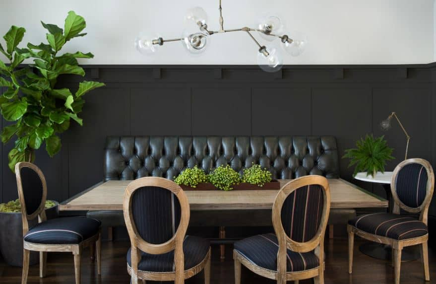 The lower half of the walls has a black wooden finish complemented by a black leather cushioned bench.
