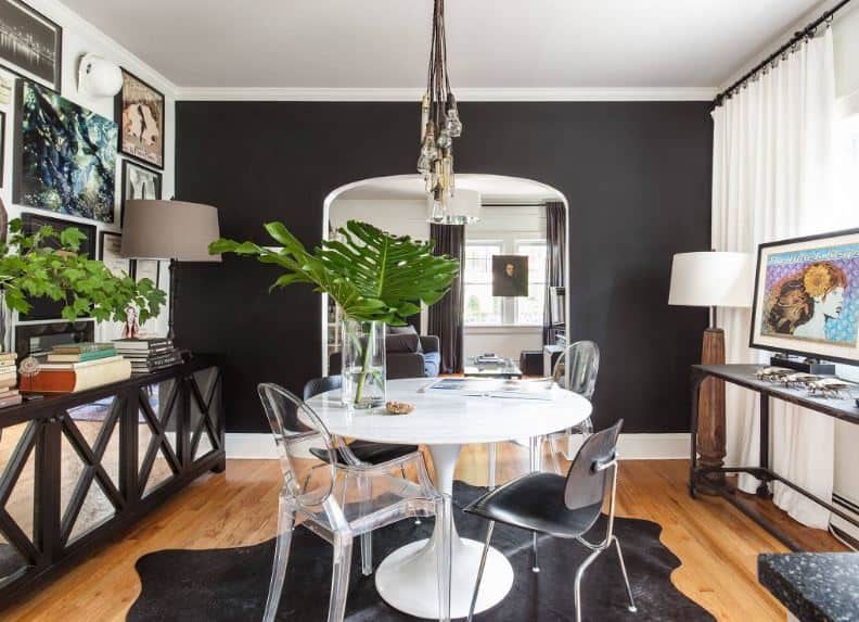 The hardwood flooring is topped with an animal black area rug that contrasts the white circular dining table surrounded by modern chairs.