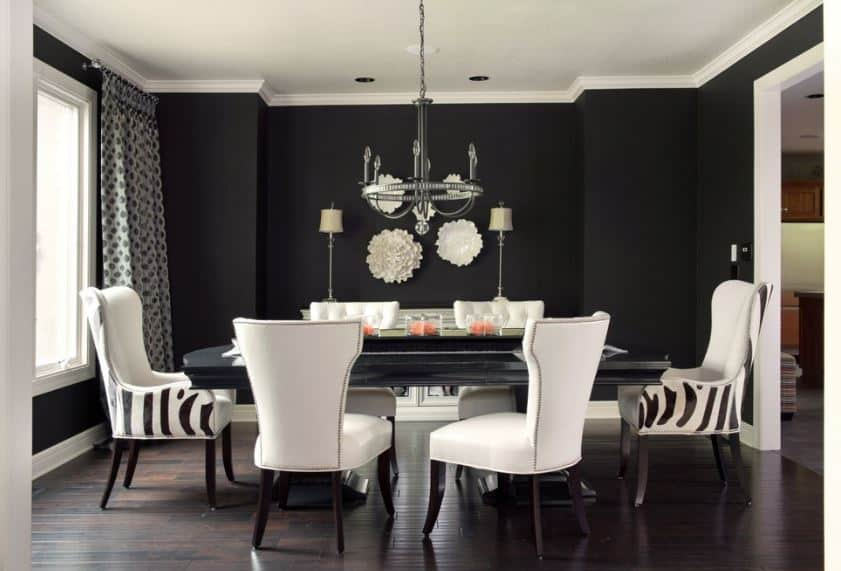 The black walls and the black wooden dining table is contrasted by the white leather chairs that match the white ceiling.