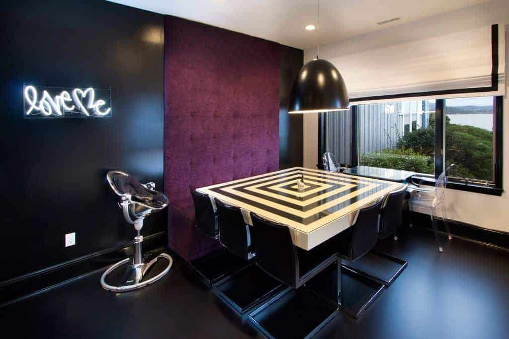The black walls and black flooring is complemented by a purple bench with a cushioned back that goes all the way to the white ceiling.