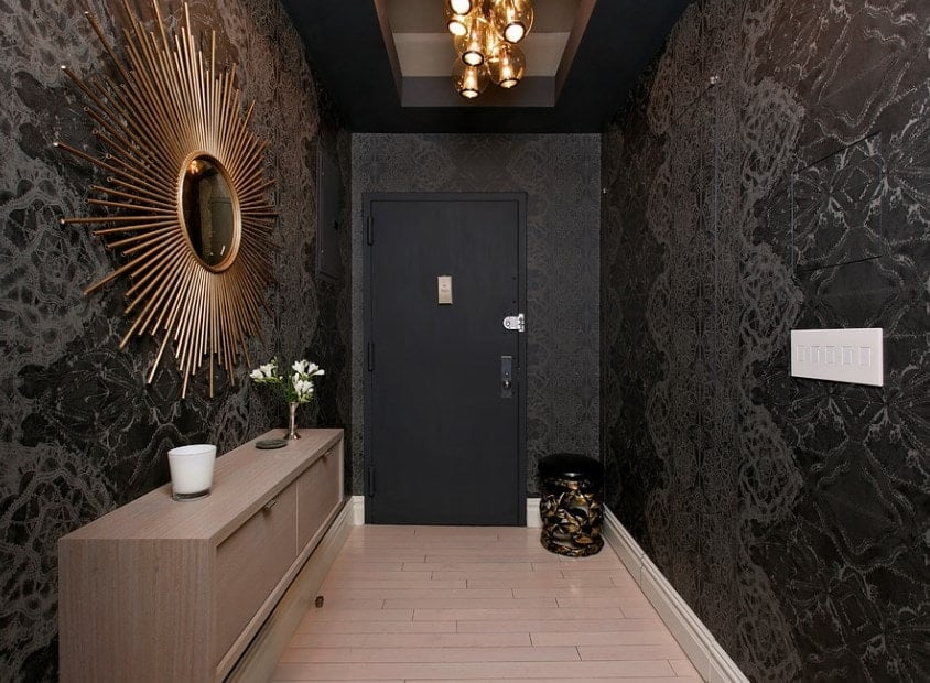 A narrow entry surrounded by elegant black walls. The stylish ceiling lighting is set on the room's tray ceiling.