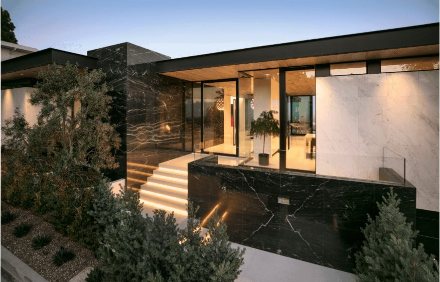 A modish black home with a gorgeous exterior and garden area.