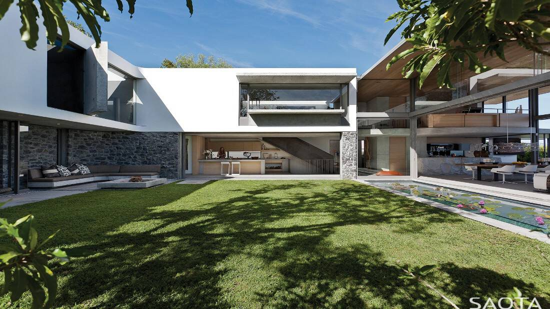 This contemporary house offers a wide lawn area along with an outdoor sofa, an outdoor dine-in kitchen and a swimming pool.