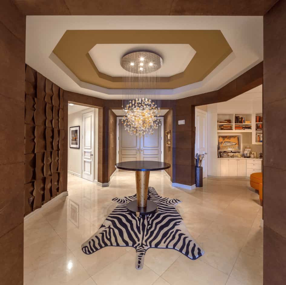 Contemporary foyer boasts a round center table that sits on a zebra rug illuminated by a fancy chandelier that hung from the tray ceiling.