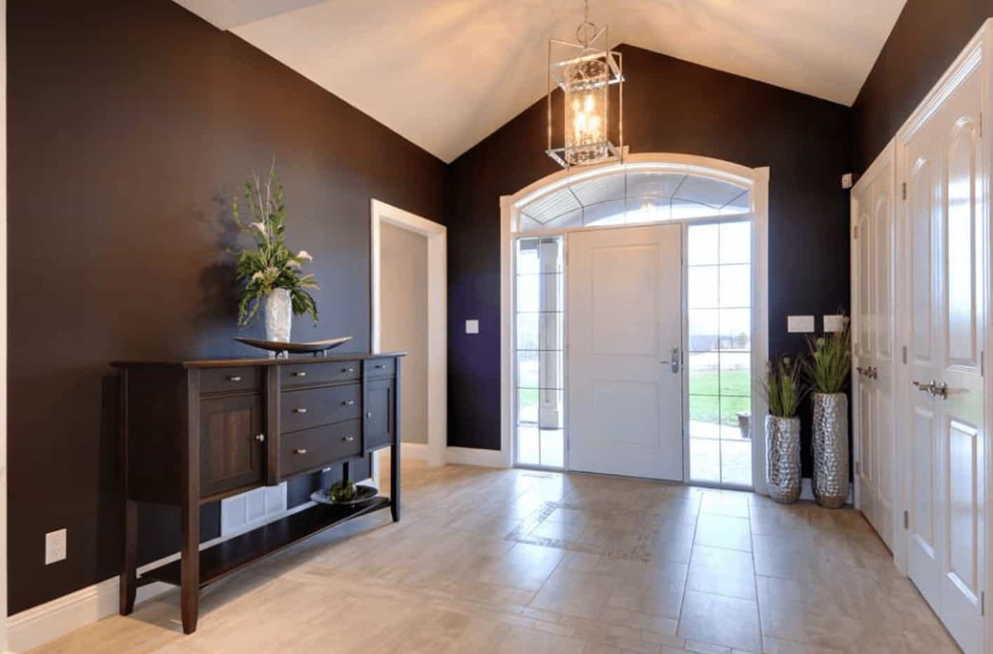Brown foyer offers tiled flooring and cathedral ceiling with a hanging pendant light. It includes silver vases and a wooden console table and fitted with drawers.