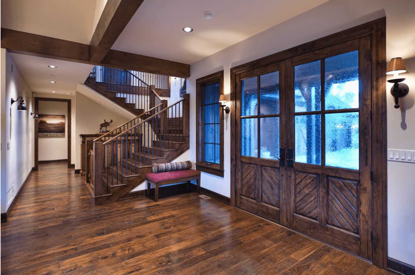 Traditional foyer with wood plank flooring and a wooden french door lighted by wall sconces. There's a red bench topped with a cylindrical pillow by the staircase.